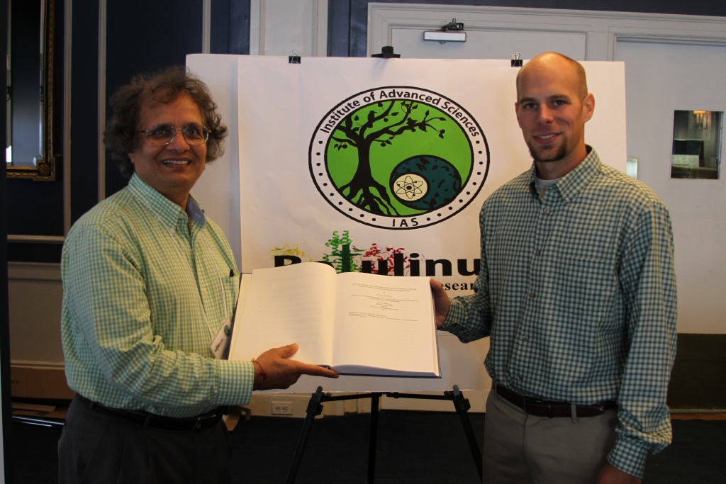 Dr. Tom Feltrup presenting a copy of his thesis to Dr. Singh